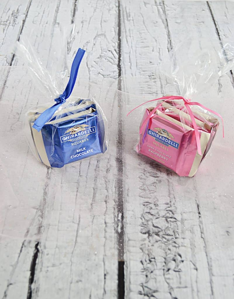 Two bags of baby shower favors. One with blue and white chocolate and the other with pink and white chocolates.
