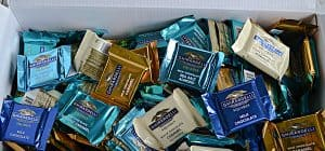 A box filled with metallix colored chocolate squares.