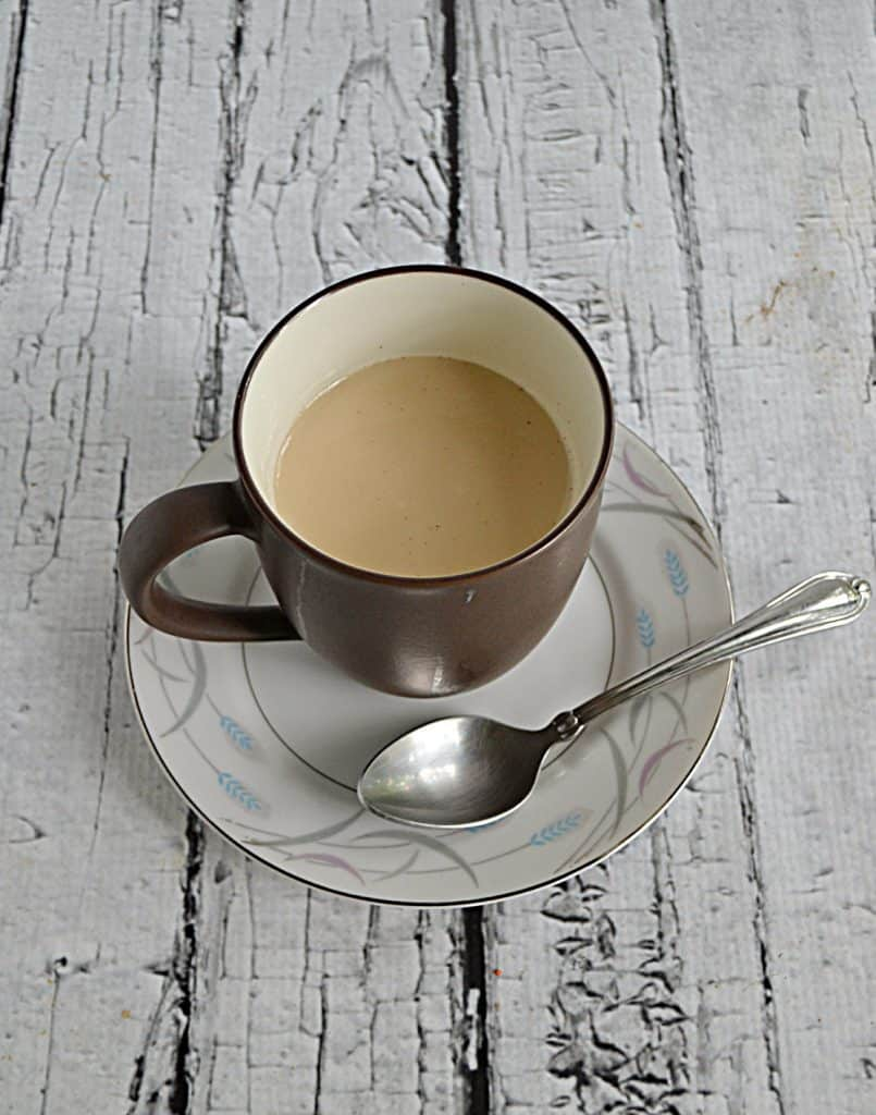 A cup of Royal Milk Tea on a saucer with a spoon on the saucer.