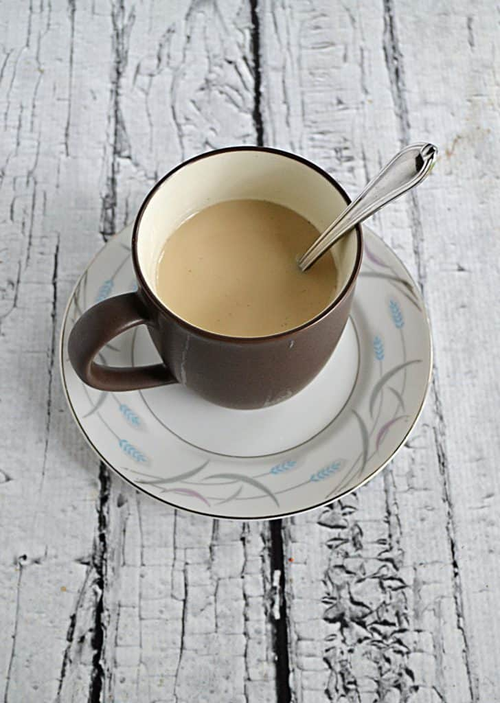 A cup of milk tea on a saucer with a spoon in the cup.