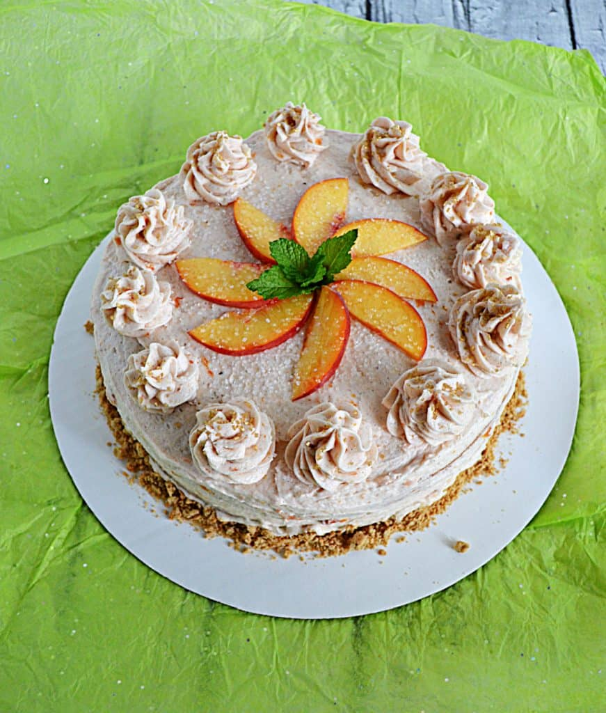 A brown sugar cake with peach vanill frosting topped off with peach slices and fresh mint.