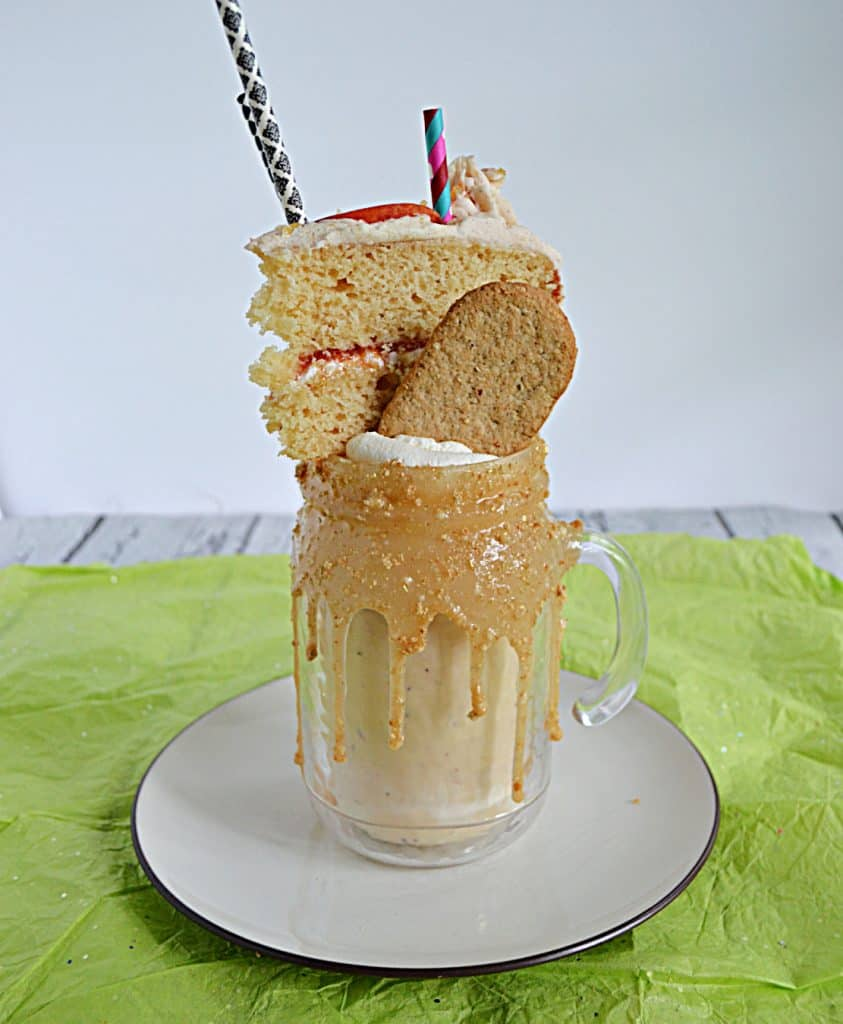A milkshake with a thick caramel rim topped off with whipped cream, a graaham cracker, a slice of cake, and two straws.