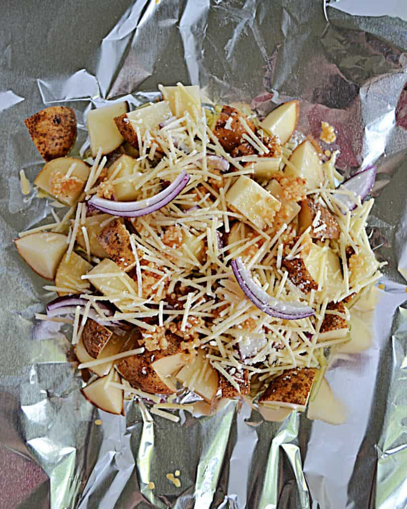 A piece of foil with uncooked potatoes, onions, garlic, and cheese in it.