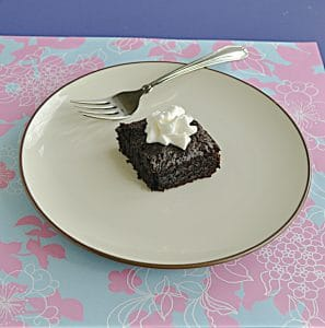 A plate with a chocolate sourdough brownie topped with whipped cream and a fork on the plate.