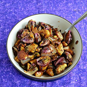 A bowl with a spoon in it and Balsamic Brussels Sprouts and Sweet Potatoes.