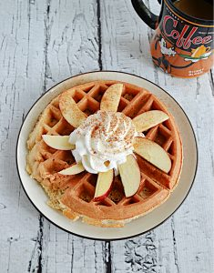 A plate with a large Apple Spice Cake Mix Waffle on it topped with apple slices, whipped cream, and cinnamon on top.