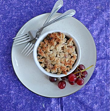 A plate with a ramekin of grape crumble on it, a pile of grapes, and two forks.