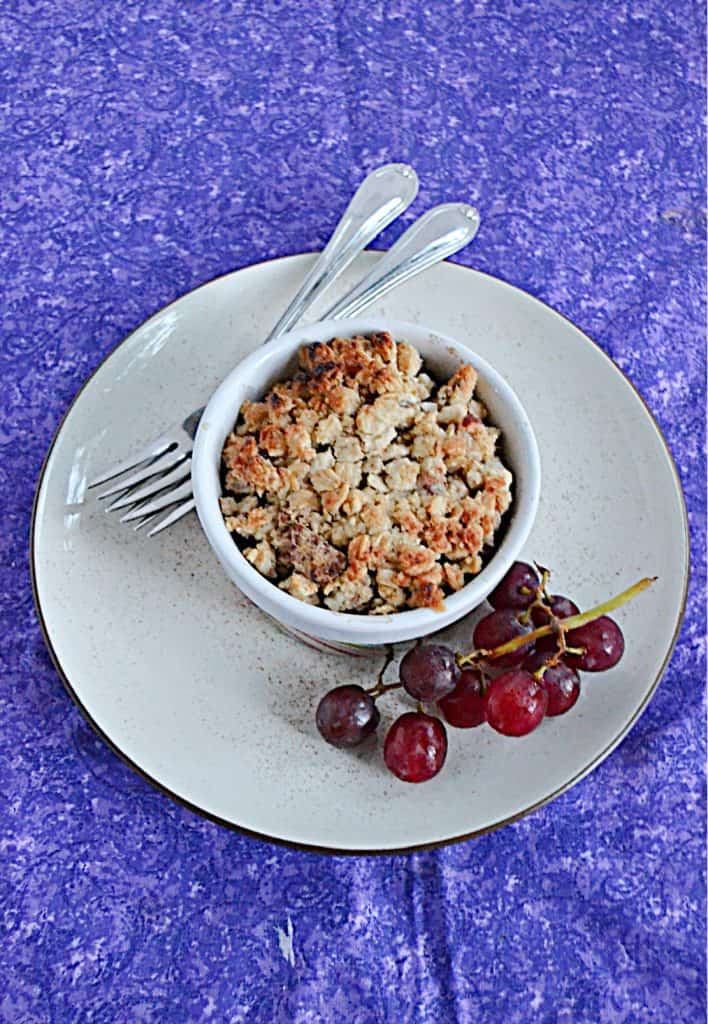 A plate with a bowl of grape crumble on it with a stem of grapes on the one side and two forks on the other side.