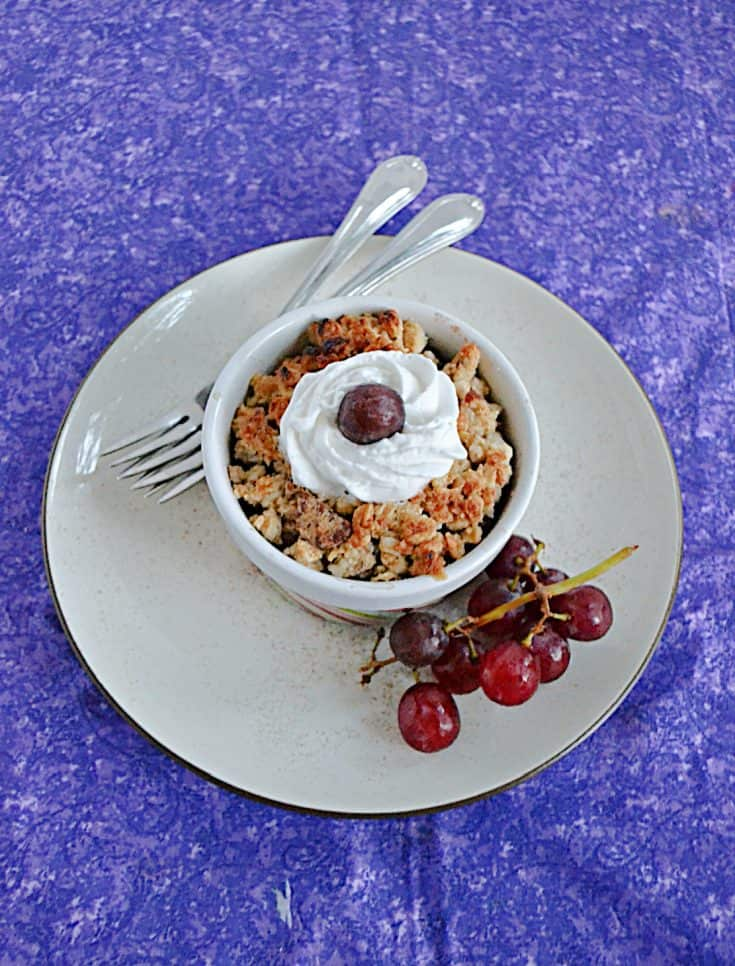 A plate with a bowl of grape crumble on it topped with a grape and whipped cream, a stem of grapes on the one side and two forks on the other side.
