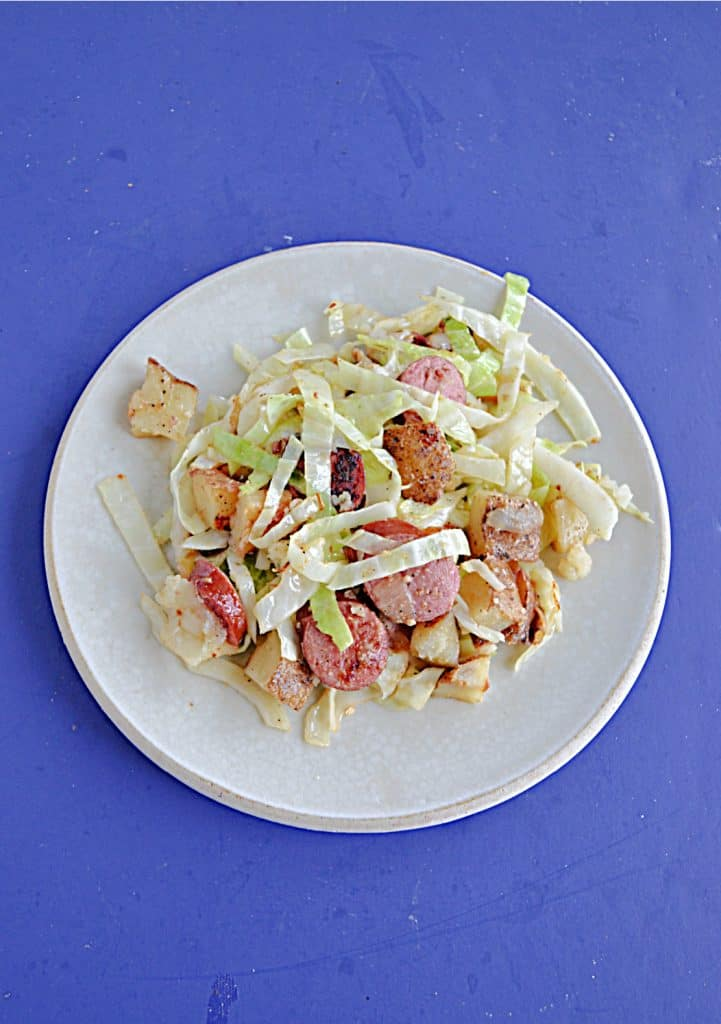 A plate piled high with cabbage, kielbasa, and potatoes.