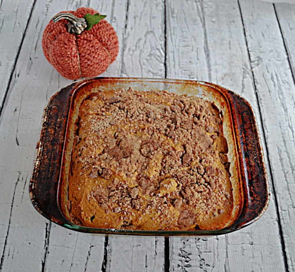 A pan of Pumpkin Spice Coffee Cake with a pumpkin behind it.