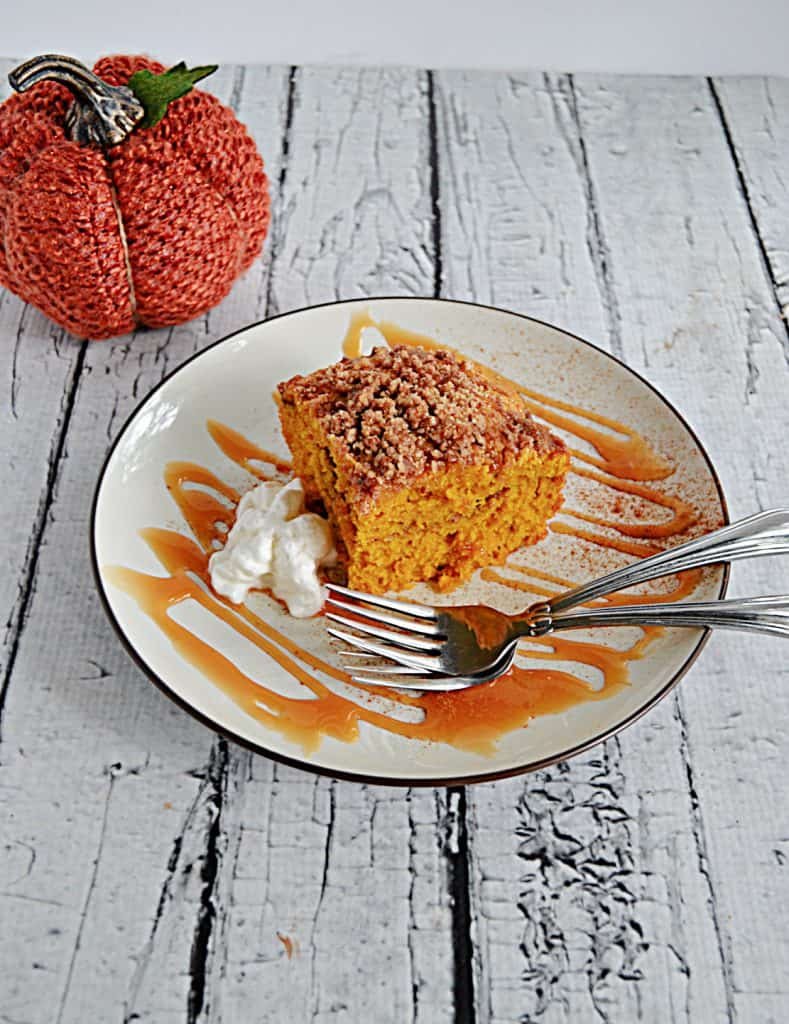A plate with a caramel drizzle, two forks, and a slice of Pumpkin Spice Coffee Cake on it.