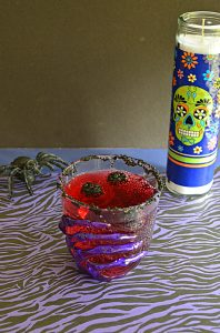 A glass with a skeleton hand on it filled with red Vampire's Kiss Cocktail and floating blackberries with a spider and a skull candle in the background.