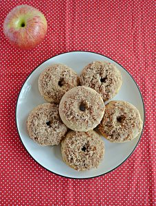 A plate topped piled high with Apple Cider Donuts rolled in pecan sugar.