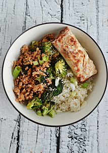 A bowl filled with ground chicken, broccoli, rice, and an egg roll.
