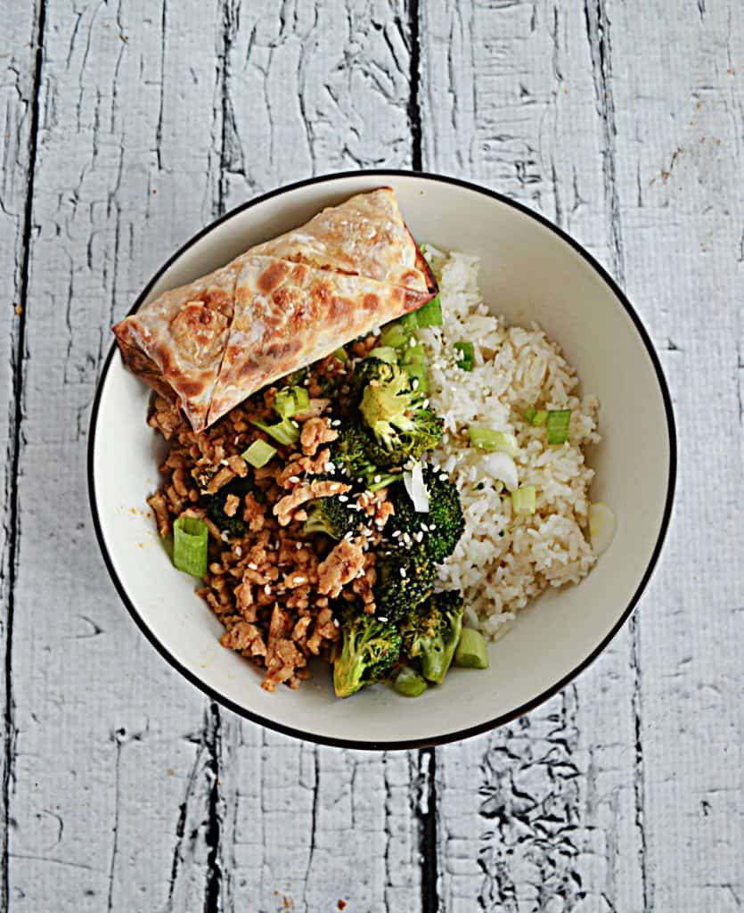 A top view of a bowl filled with ground chicken, broccoli, and rice with an egg roll.