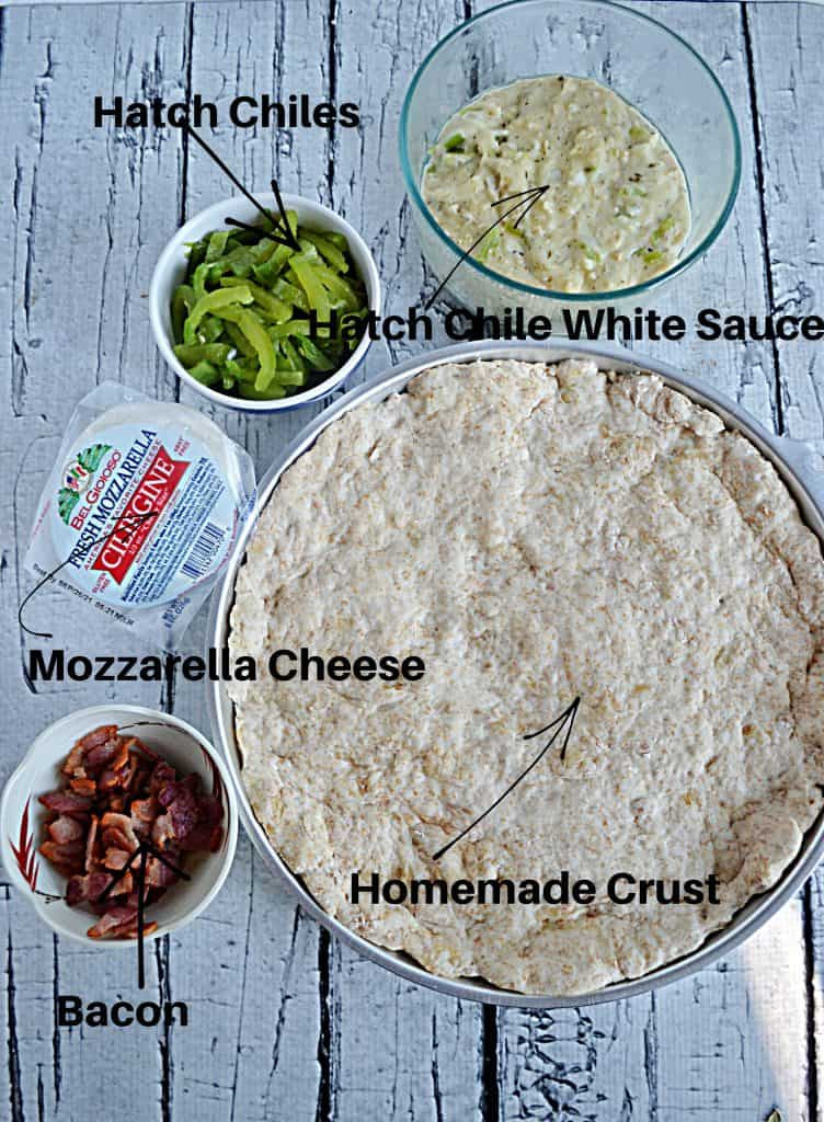 A pizza pan with pizza dough in it, a bowl of white Hatch Chile suce, a bowl of Hatch Chiles, mozzarella balls, and a bowl of crispy bacon.