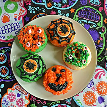 A plate with 5 orange and green Halloween Monster Donuts on it.