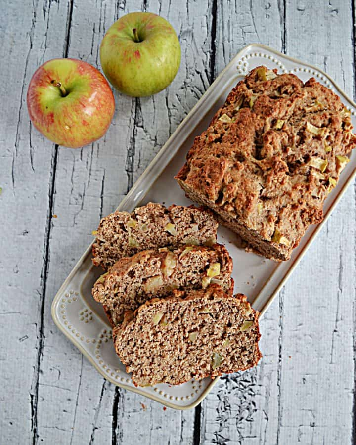 A platter with three slices of apple banana bread and the rest of the loaf with 2 apples in the background.