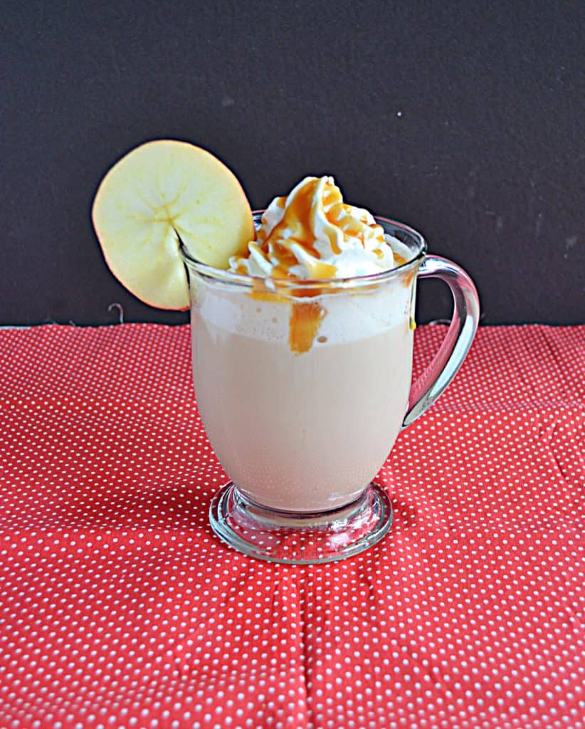 A side view of an Apple Chai Tea Latte with whipped cream and caramel on top and an apple wheel on the lip of the glass.