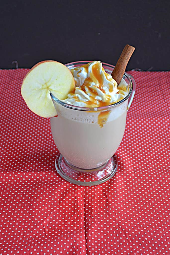 an Apple Chai Tea Latte with whipped cream and caramel on top and an apple wheel on the lip of the glass and a cinnamon stick stuck in it.