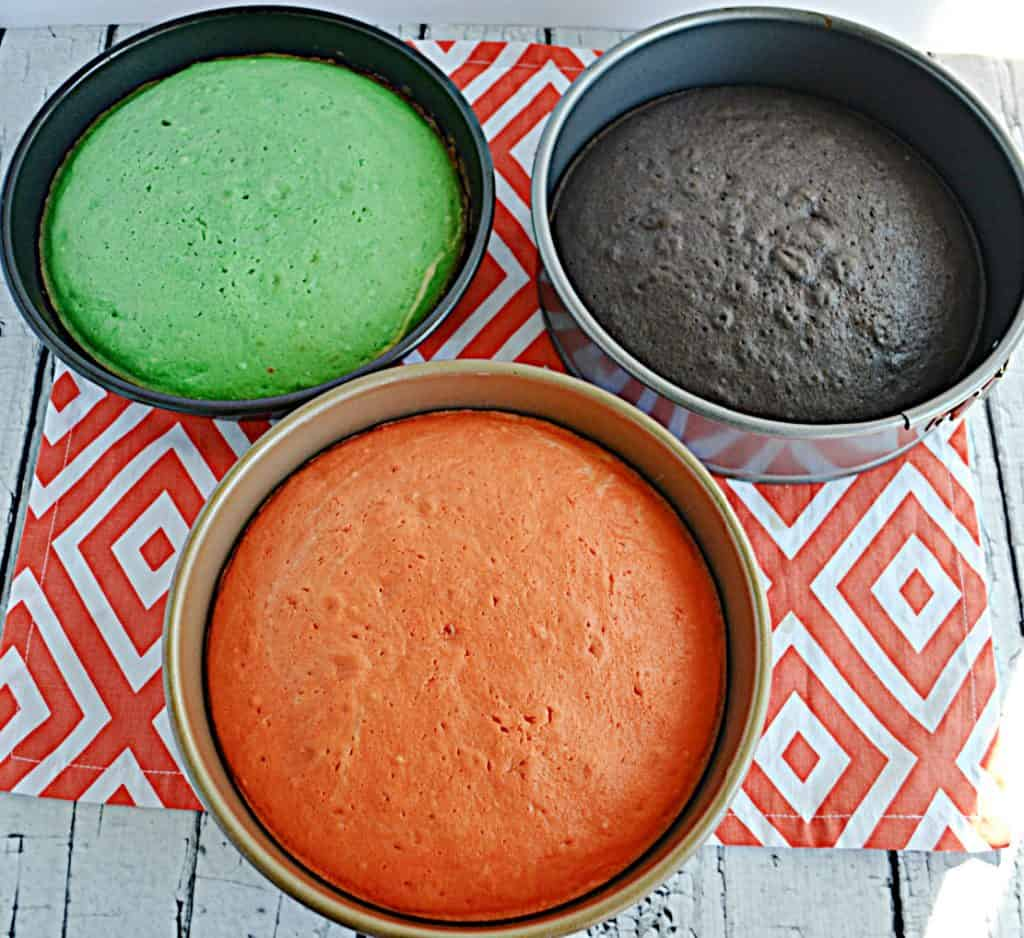 Three cake pans.  One with orange cake, one with a green cake, and one with a black cake.