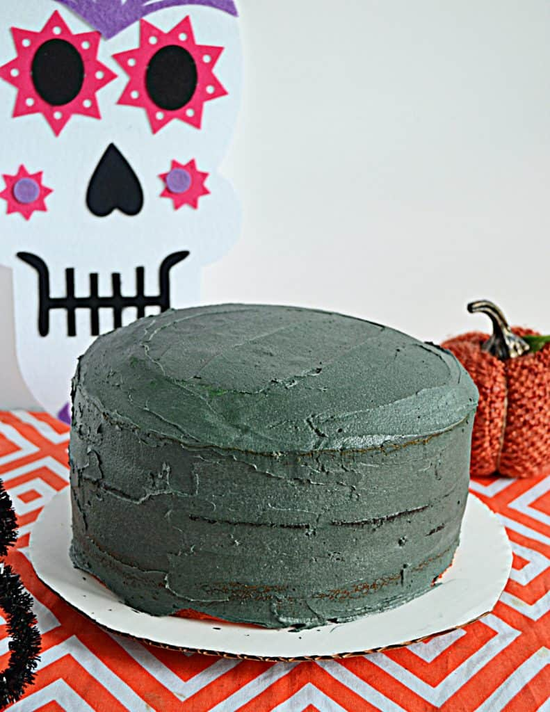 A layer cake topped with black buttercream and a skull decoration behind it.