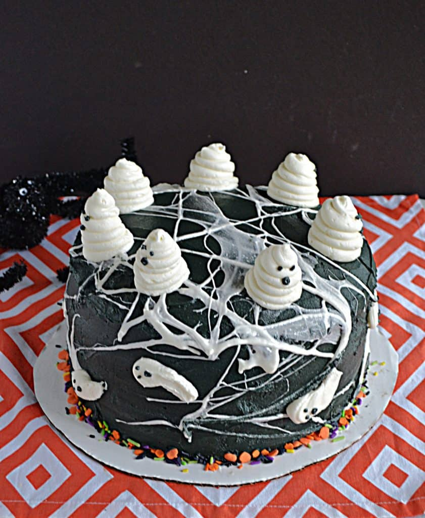 A black cake covered in marshmallow spiderwebs and swirled buttercream ghosts on top.
