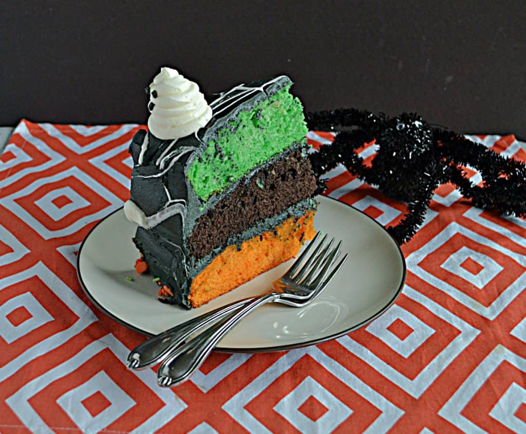 A close up of a slice of cake with a green, orange, and black layer, with two forks on the plate and a fake spider crawling onto the plate.