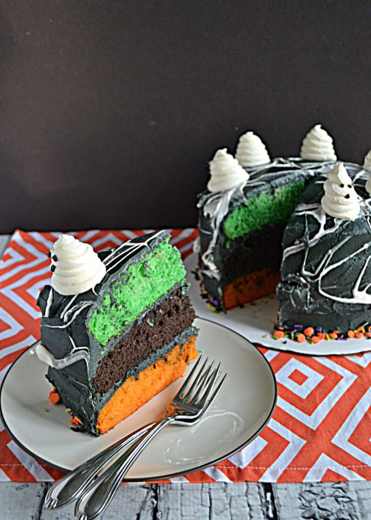 A  slice of cake with a green, orange, and black layer, with two forks on the plate and the whole cake sitting behind it with the slice cut out.