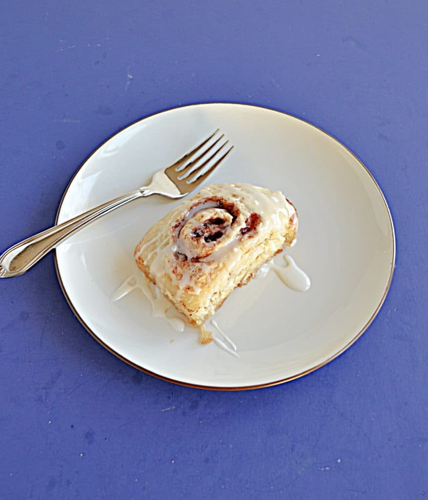 A plate with a cinnamon roll topped with vanilla icing and a fork on the plate.